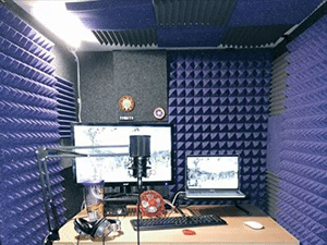 A desk setup with equipment for recording voice-overs inside of a WhisperRoom booth