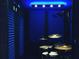 the interior of a WhisperRoom drum room with blue studio foam on the wall and a full drum kit