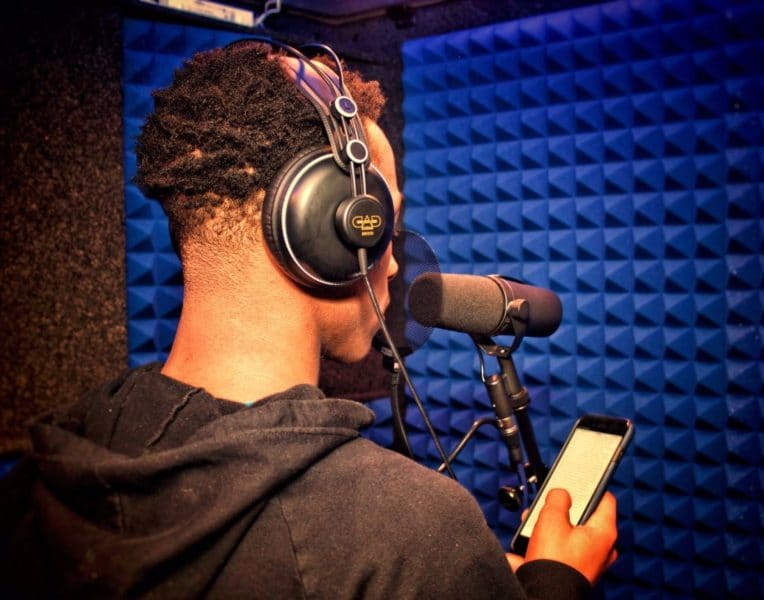 A young man wearing headphones and speaking into a microphone while recording inside of a WhisperRoom portable vocal booth