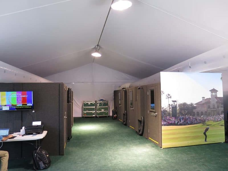 Several broadcast booths set up inside a tent for international broadcast