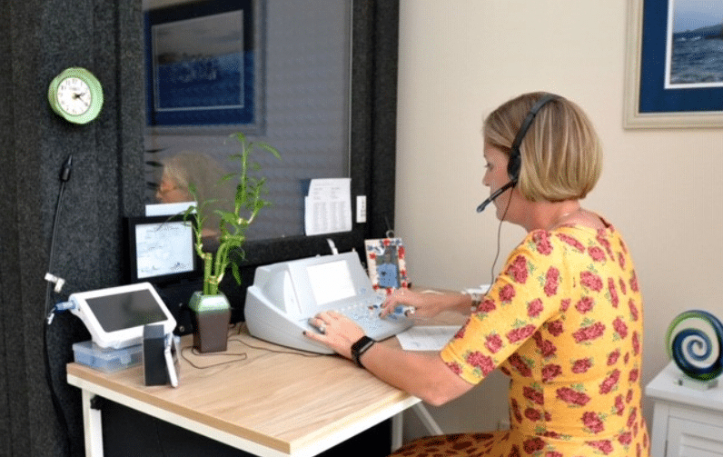 Image of a Audiologist wearing a headset and sitting at a desk while conducting an audiometric test for a patient