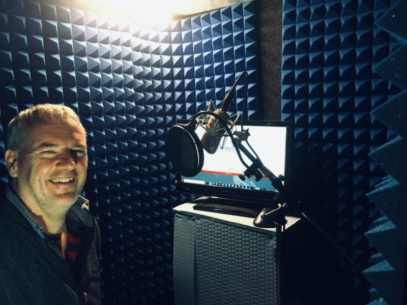 Professional voice actor Ian Russell smiling next to his microphone setup, inside of his home studio's portable vocal booth.