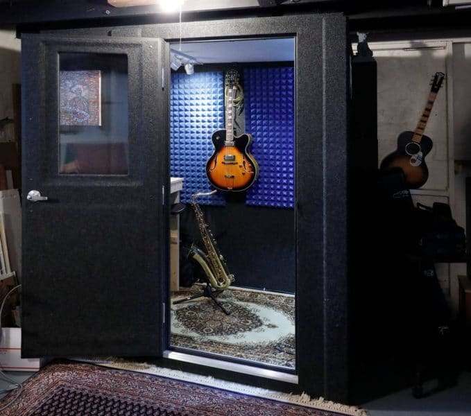 Musician Tim Rummelhoff's WhisperRoom practice booth with a guitar mounted on the wall and a saxophone on a stand