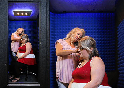 two women inside of an audiology booth performing a hearing test