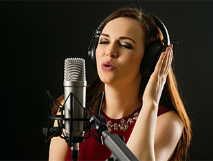 A picture of a woman singing into a microphone