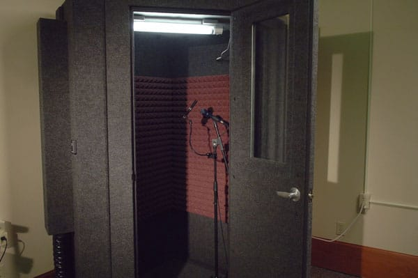 image of a WhisperRoom sound isolation booth with an open door and microphone inside