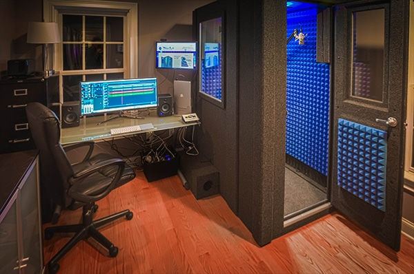 One of WhisperRoom's recording booths in a home studio with audio gear directly outside the wall window