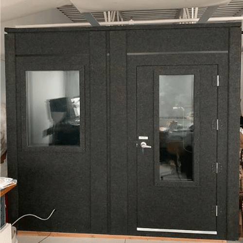 The front wall and door to a 8.5'x10.5' WhisperRoom sound isolation booth