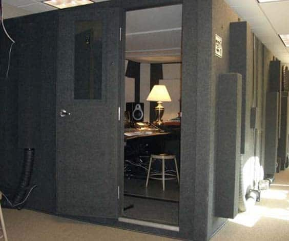 A 8.5'x12' WhisperRoom with a mixing board, stool, and lamp inside