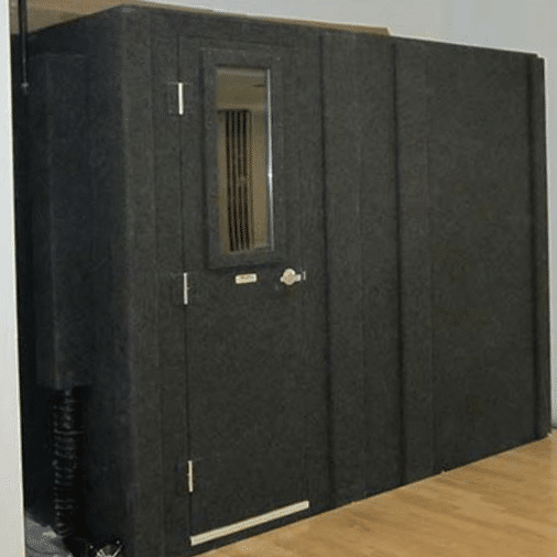 A 8.5'x7' WhisperRoom isolation booth on hardwood floor in a studio