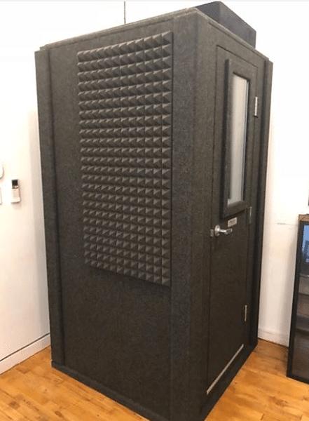 A 3.5'x3.5' WhisperRoom isolation booth on a hardwood floor