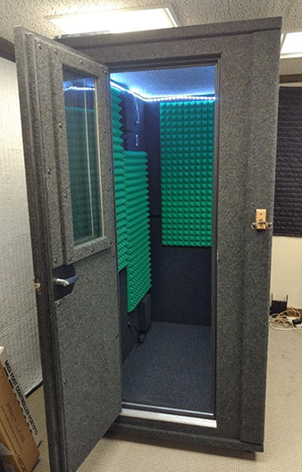 A 3.5'x5' WhisperRoom booth with green acoustic foam inside