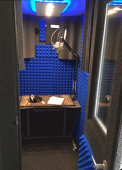 image of the inside of a whisperroom booth equipped with a desk, lamp, and blue foam