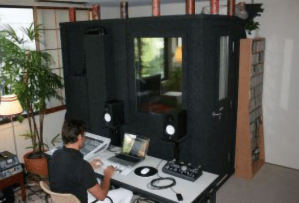 image of man editing audio with a whisperroom isolation room in the background