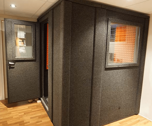 A 6'x6' WhisperRoom soundproof booth inside of a recording studio