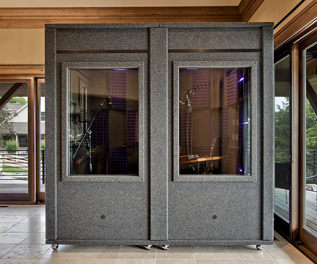 Front view of a 6'x8' WhisperRoom sound isolation room with two large windows inside the foyer of a home