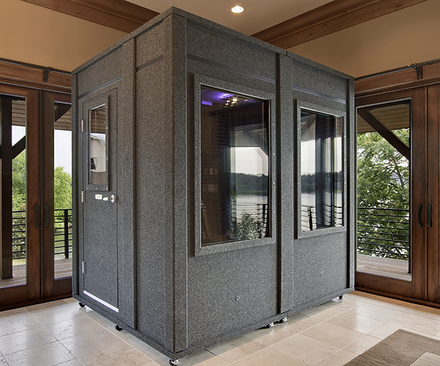 Angled view of a 6'x8' WhisperRoom sound isolation room with two large windows inside the foyer of a home