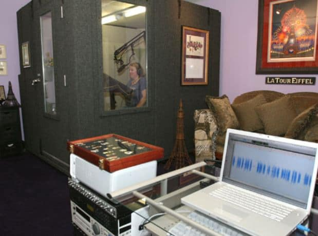 A woman doing voiceovers inside of a 6'x8' WhisperRoom in a home office