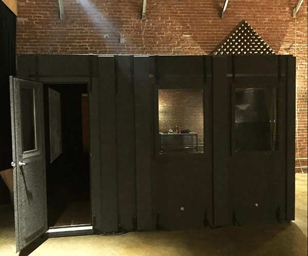 An 8'x12' WhisperRoom booth in a recording studio with a brick wall background