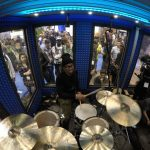 A crowd looks through windows to observe a drummer inside of Go-Pro's custom built WhisperRoom at the 2016 NAMM Show