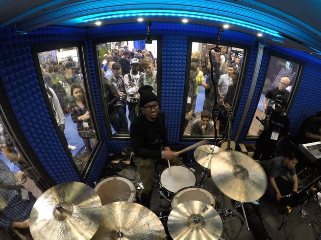 A crowd looks through windows to observe a drummer inside of Go-Pro's custom built drum booth at the 2016 NAMM Show