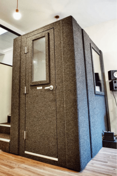 A WhisperRoom Isolation booth inside of a home studio on a hardwood floor