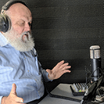 man with gray beard recording his voice