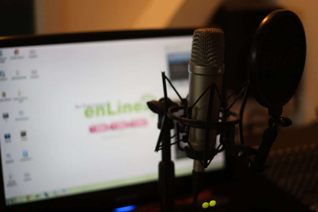 A condenser microphone in front of a turned on computer monitor