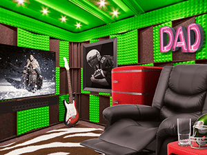 a recliner, tv, guitar, and mini fridge set up inside of a soundproof WhisperRoom man cave