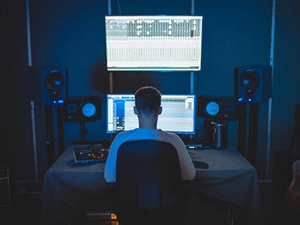 a recording engineer sitting in a chair looking at his computer monitor