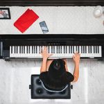 woman playing piano inside of a room
