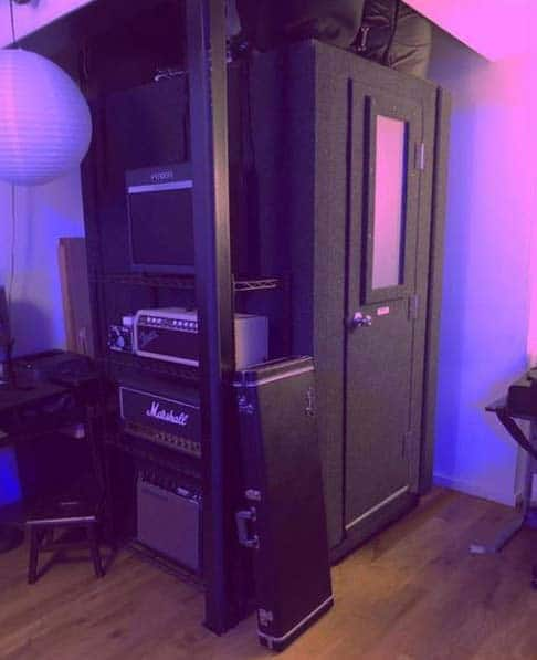 A 4' x 4' WhisperRoom vocal booth cornered in a room with guitar amps