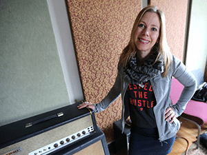 Studio manager Jessica Tomasin posing next to a guitar amp
