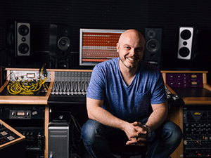 Justin Cortelyou sitting in front of his studio's mixing board