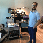 Mastering engineer Ryan Smith standing next to a collection of audio gear