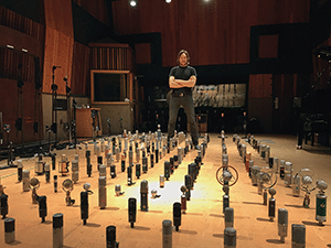 Alex Oana standing next to hundreds of microphones inside of a room