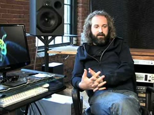 Producer Craig Alvin sitting next to his studio gear while having a conversation