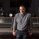 Recording producer Steve Genewick leaning on his mixing console in a studio