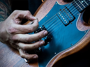 close up a man playing a Gibson SG
