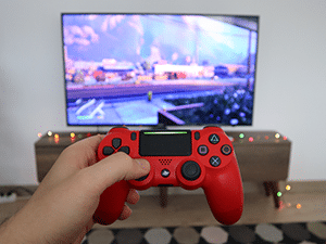 Hand holding video game controller in front of a TV