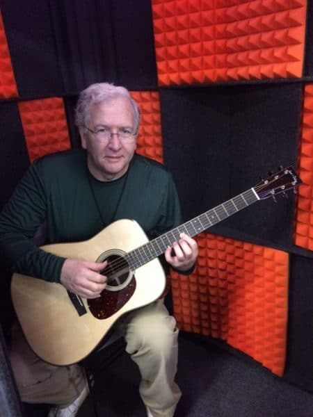 Man playing acoustic guitar inside a WhisperRoom