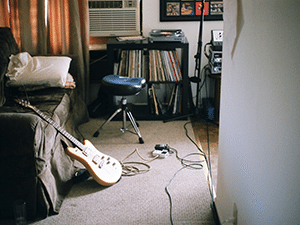An electric guitar leaning on a bed next to a stack of records