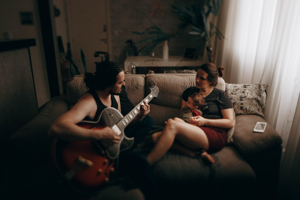 A man playing guitar on the couch with wife and baby sitting next to him