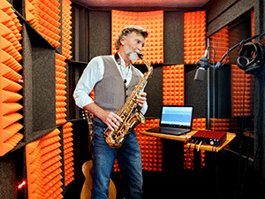 Image of a man recording saxophone inside of his WhisperRoom soundproof booth