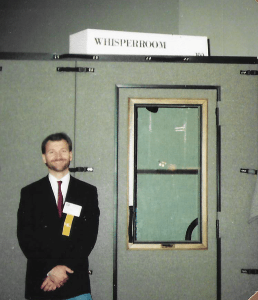 WhisperRoom's founder standing next to an original booth at a tradeshow