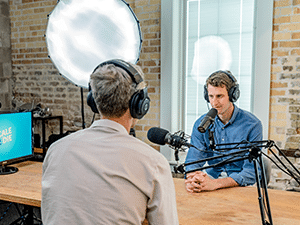Two men sitting at a desk and recording a podcast