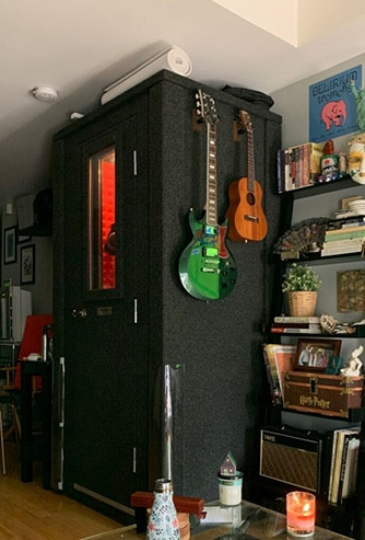 A WhisperRoom in an apartment with guitars hanging on the exterior wall.