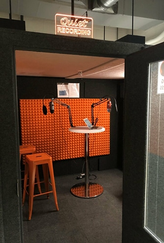 Cornell's WhisperRoom shown with door open and podcasting gear inside.