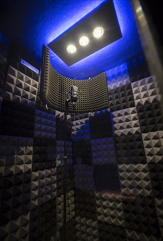 The interior of a WhisperRoom vocal booth with acoustic foam on all walls and a condenser mic.