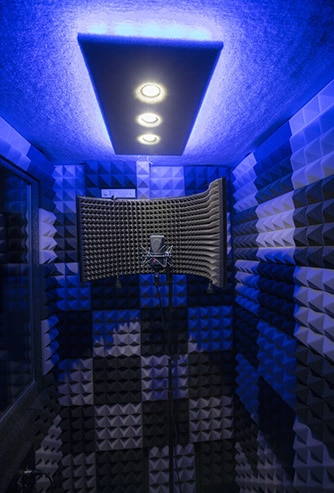 A WhisperRoom vocal booth with a blue studio light and a microphone setup inside the booth.